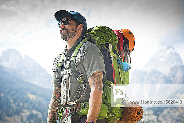 Male Hiker Standing In Front Of The Grand Teton Mountains In Jackson Hole  Wyoming