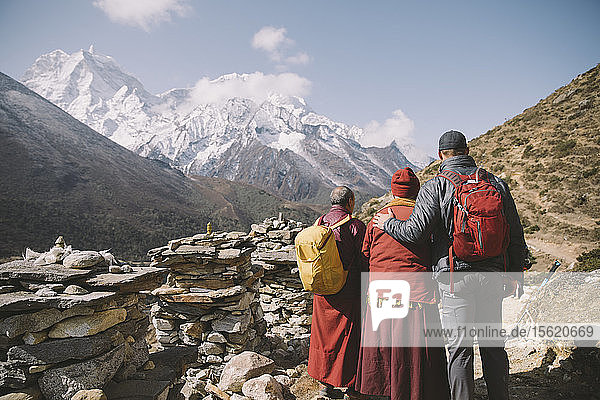 Two Buddhist monks pose with a Himalayan trekker in the Everest Region.