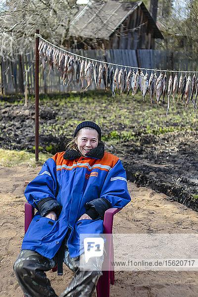 Portrait of blonde woman sitting on chair in winter coat  Tikhvin  Saint Petersburg  Russia