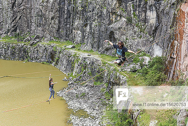 View from above of adventurous man and woman walking on slackline  Dibs Quarry  Maripora  Sao Paulo State  Brazil