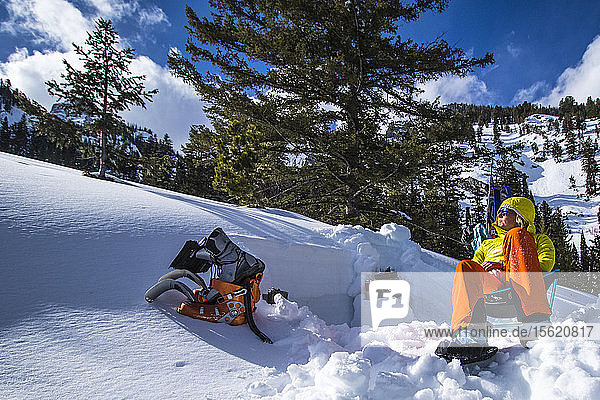 A Young Woman Relaxing After Ski Touring And Digging Avalanche Pits