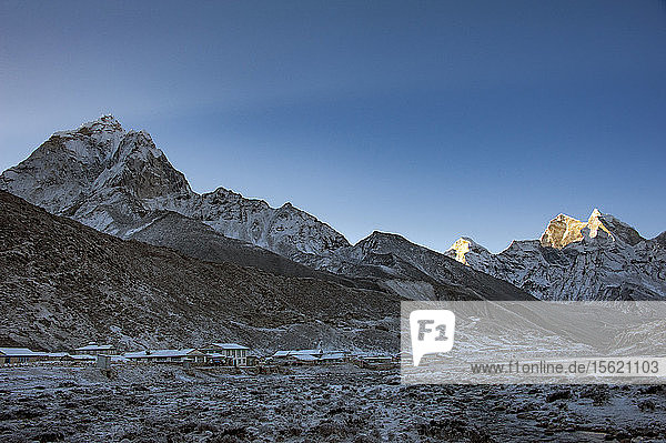 Mountain village and Ama Dablam mountain at winter dawn  Solukhumbu  Nepal