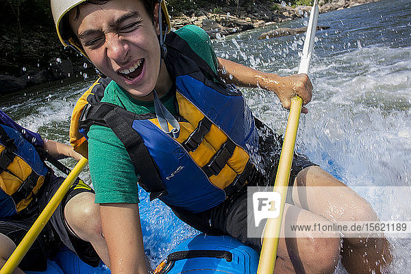 Order of the Arrow scout Noah Lopez gets splashed with a wave while paddling a raft with fellow scouts through a rapids on the New River  during a whitewater adventure in the New River Gorge  near Fayetteville  outside of the Summit Bechtel Reserve (SBR)  WV. The OA scouts are participating in a service and adventure program at SBR.