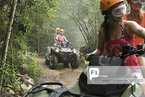 Women driving quad bikes in Emotions Native Park during rain  Quintana Roo  Mexico