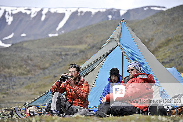 Team enjoys drier climates at base camp while they wait for better wheather conditions during a ski ascent of Mount Sanford Sheep Glacier Route in the Wrangell-St. Elias National Park outside of Glennallen  Alaska June 2011. Mount Sanford at 16 237 feet is the sixth tallest mountain in the United States. (Model Release: Patrick Gilroy  Adam Howard  and Agnes Hage)