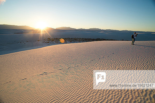 A photographer takes pictures in White Sand Dunes National Park at sunset in New Mexico.