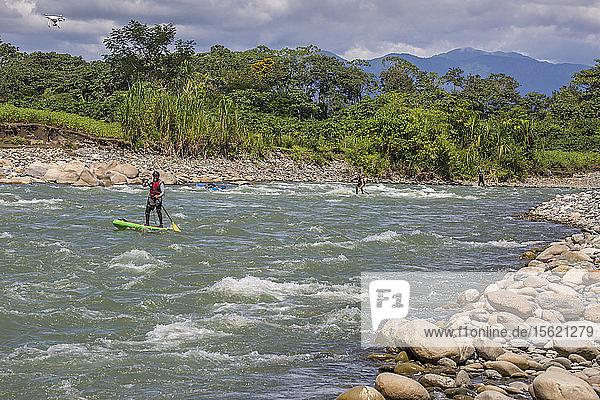 Photograph of men paddleboarding on stand-up paddleboards  Peruvian Amazon  Manu National Park  Peru