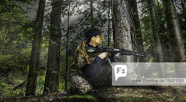 Girl in a military uniform in a low position with electric gun that shoots plastic balls  on airsoft competition in central Serbia.