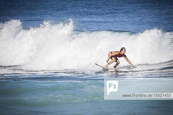 Full length shot of woman surfing in sea