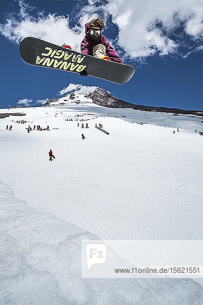 A snowboarder hitting a quarterpipe jumping over Mt. Hood