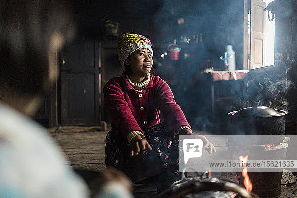 Young woman crouching in front of indoor campfire and warming hands  Myanmar  Shan  Myanmar