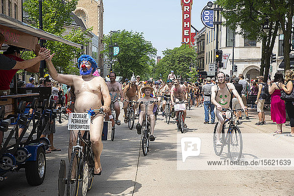 Large number of naked cyclists riding along street to protest dependence on fossil fuels  Madison  Wisconsin  USA