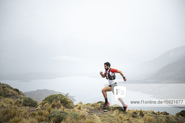 Side view shot of man trail running in natural setting in Torres del Paine National Park  Magallanes region  Chile