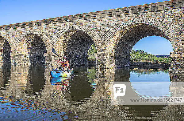 Angler paddles under a bridge on the Brazos River