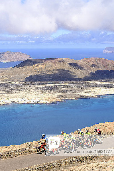 Group of cyclists pedaling on coastal road  Timanfaya National Park  Lanzarote  Canary Islands  Spain