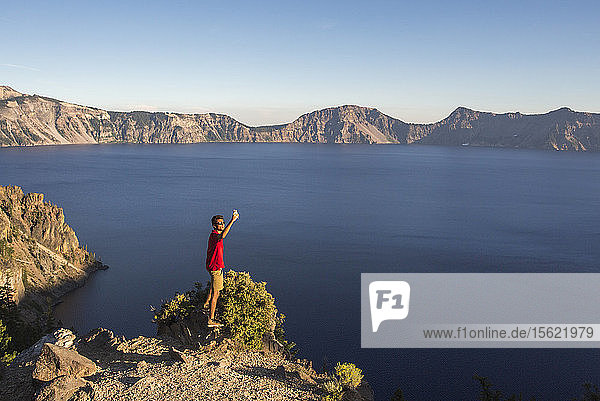 A young man in a red shirt poses for a selfie on a rock outcrop high above a deep blue lake surrounded by mountains  Crater Lake  Oregon  USA