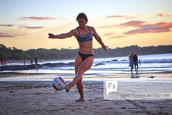 Soccer player practices on the beach at sunset