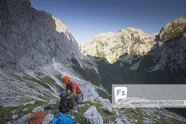 A mountain guide is sorting out gear at the beginning of climbing the famous north face of the Triglav  the highest peak in Slovenia