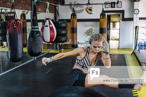 Photograph of young woman in gym kicking while practicing kickboxing  Seminyak  Bali  Indonesia