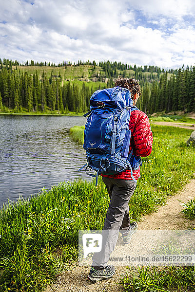 Rear view shot of female backpacker hiking on lakeshore  Bolam Pass  Colorado Trail  Colorado  USA