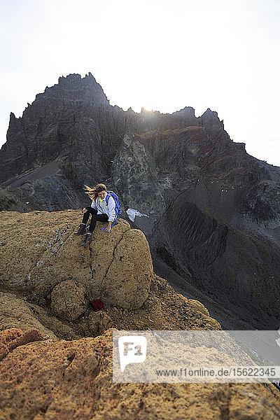 Female Hiker hiking along a rock formation in front of 3 fingered jack.