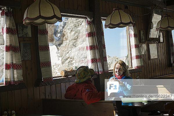 Ein Paar mit einem Kaffee im Inneren Rifugio Lorenzi in der Cristallo Mountain Range