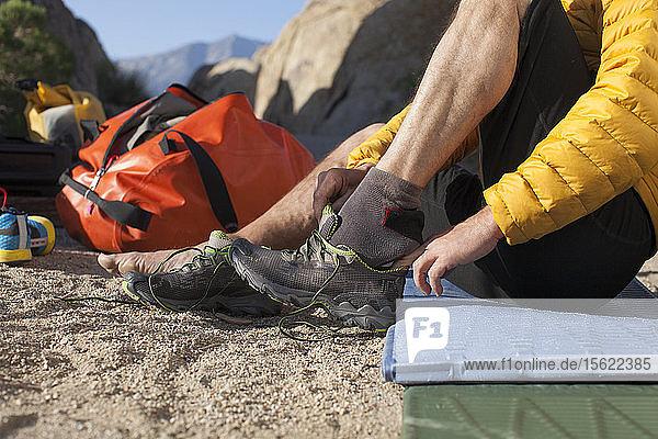 Mann setzt auf Schuh während der Vorbereitung für Trail Running in Alabama Hills National Recreation Area  Kalifornien  USA