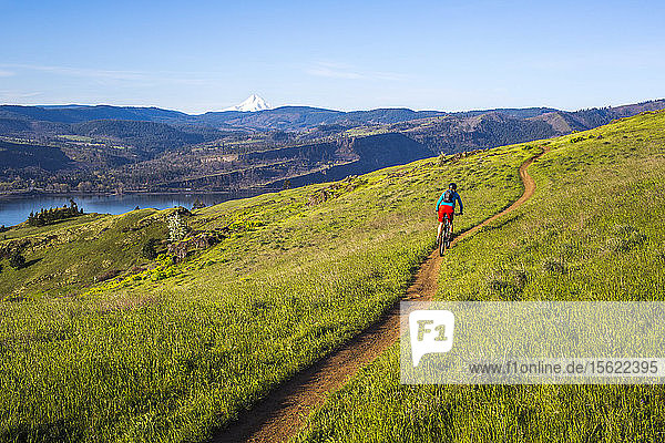 A young woman rides a mountain bike on a single-track trail through green grass with a large river in the distance.