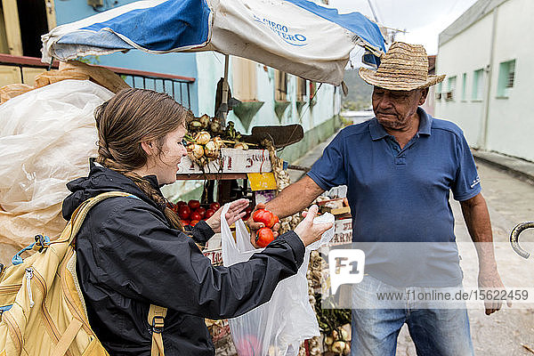 Woman buying vegetables from local man owning outdoor stall  Baracoa  Cuba