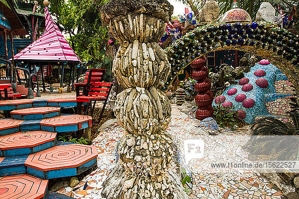 Colorful structures and rooms at the Jade Seahorse - an eclectic  artsy compound of rooms for rent  a bar in a treehouse  kooky structures  walkways and bridges on Utila Island  Honduras.