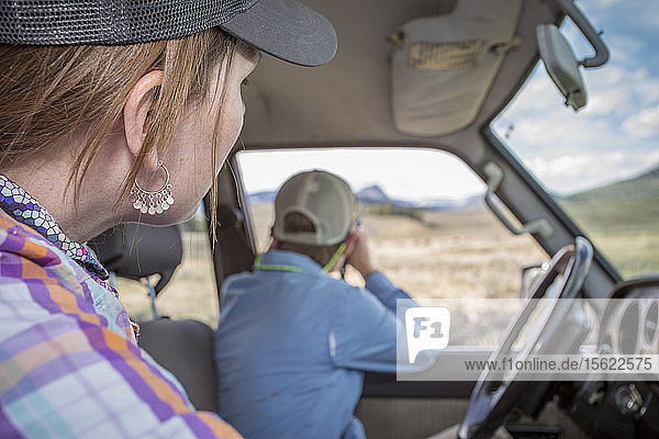 Woman spot wildlife from their Land Cruiser in Yellowstone Country.