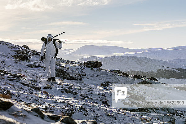 A Photographer Carrying A Tripod Across His Back Walking On Snowy Landscape