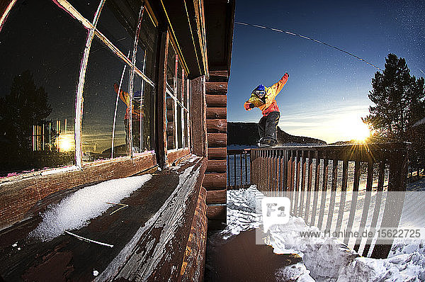 A snowboarder switch nose-presses the railing of a cabin in the Tensleep  Wyoming wilderness.