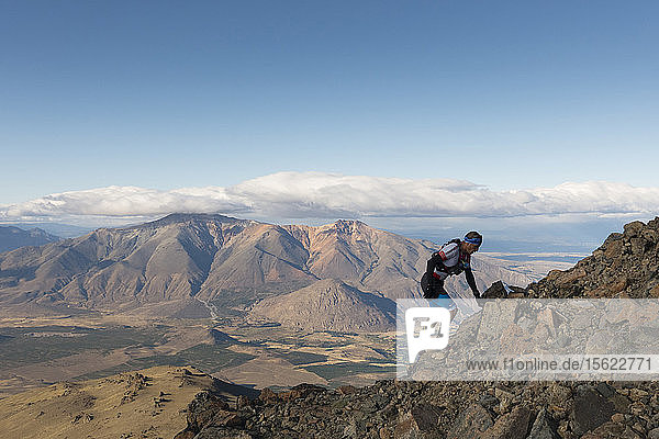 Man climbing rocky mountain against clouds and sky  Esquel  Chubut  Argentina