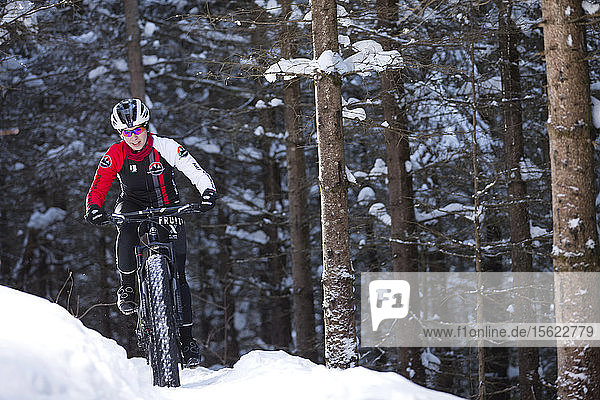 Rocky Mountain professional biker during winter training session on Fat Bike in mountain trail of Quebec  Canada