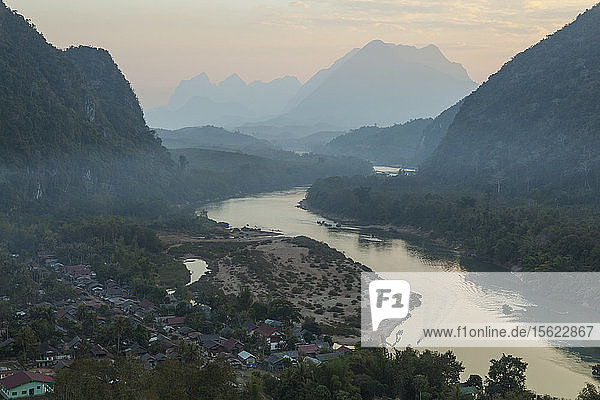 A boat motors into port at Muang Ngoi  Laos  a town on the Nam Ou River set in a spectacular karst landscape.