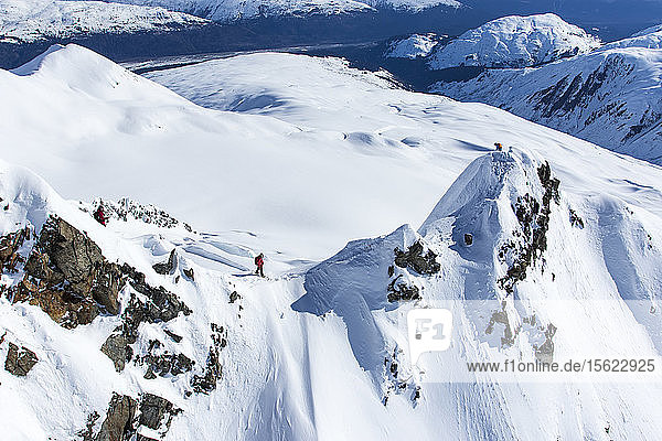 Professional Snowboarder Marie France Roy  Robin Van Gyn  and Helen Schettini  stand on top of a mountain and get ready to drop in on their snowboards after being dropped off by a helicopter on a sunny day in Haines  Alaska.