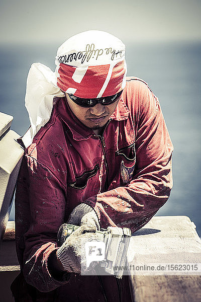 Seaman sanding a railing on a container ship while at sea.
