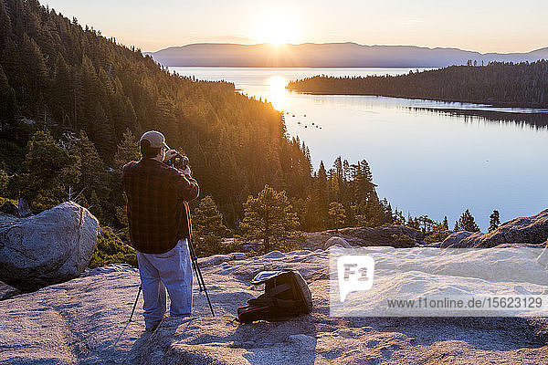 Photographer taking pictures of sunrise at Emerald Bay in Lake Tahoe  California  USA