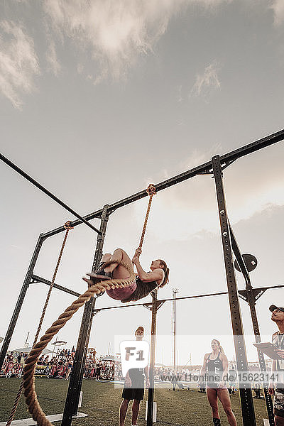 People watching female athlete climbing rope