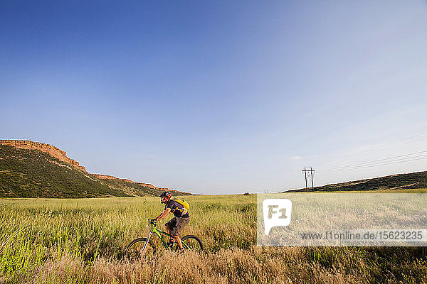 Mountain Biker rides the Blue Sky Trail while wearing a New Belgium Brewing bike jersey. He is near where Coyote Ridge Trail intersect the Blue Sky Trail  Fort Collins  Colorado.