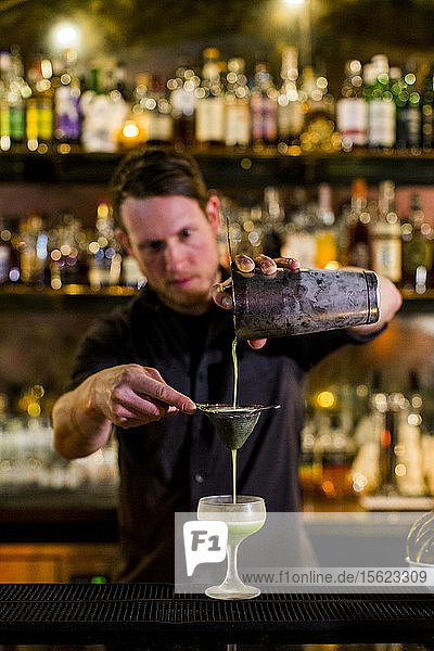 A bartender makes a fancy cocktail at a swanky bar in Seattle's Capital Hill neighborhood.