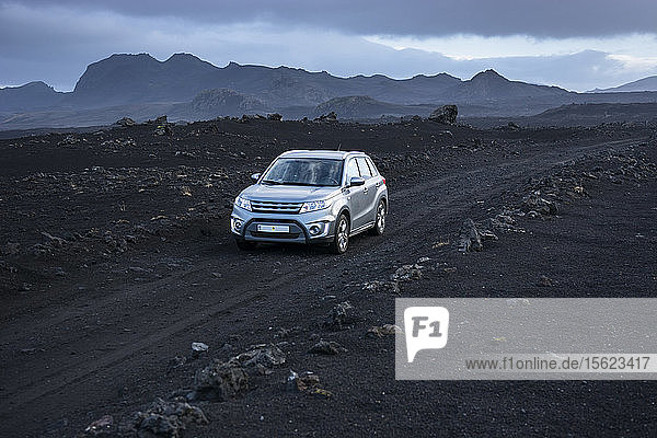 Silver-colored 4x4 SUV driving along dirt road in volcanic landscape  Sprengisandsleid  Iceland