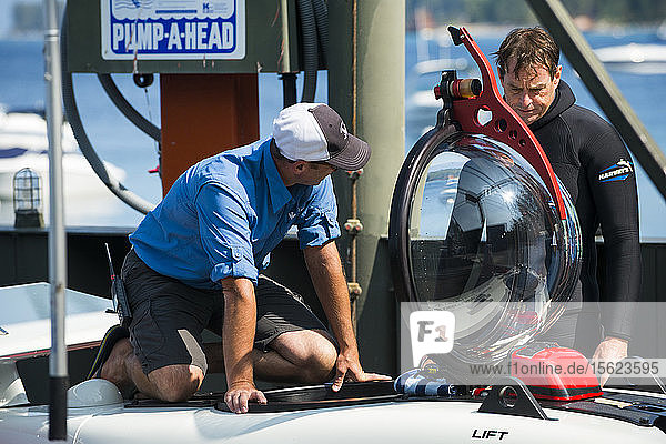 Two men preparing prototype personal two-man submarine for test dive  Homewood Marina  Lake Tahoe  California  USA