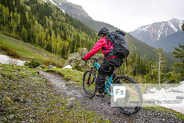Female mountain biker in scenic landscape riding in the rain on the Ice Lakes trail  USA