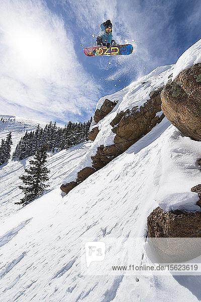 Female Snowboarder Jumping On Rock In Colorado