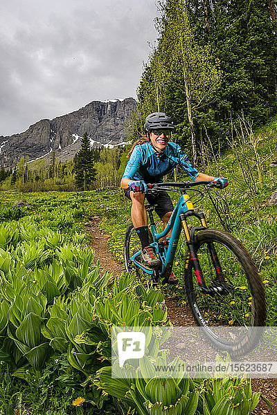 Female biker smiling while downhill riding on Ice Lakes Trail  Colorado  USA