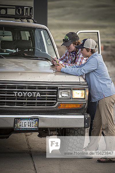 Two girls text on their phones while at a rural Montana gas station with a 1990 Toyota Land Cruiser.