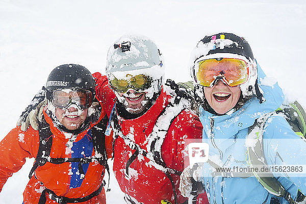 One female and two male ski freeriders are smiling with snow covered faces in the ski resort Niseko United on the Japanese island of Hokkaido. Niseko United is comprised of four resorts on the one mountain  Annupuri (1 308m). 100km south of Sapporo  Niseko Annupuri is a part of the Niseko-Shakotan-Otaru Kaigan Quasi-National Park and is the most eastern park of the Niseko Volcanic Group. Hokkaido  the north island of Japan  is geographically ideally located in the path of consistent weather systems that bring the cold air across the Sea of Japan from Siberia. This results in many of the resorts being absolutely dumped with powder that is renowned for being incredibly dry. Some of the Hokkaido ski resorts receive an amazing average of 14-18 meters of snowfall annually. Niseko is the powder capital of the world and as such is the most popular international ski destination in Japan. It offers an unforgettable experience for all levels of skier and snowboarder.