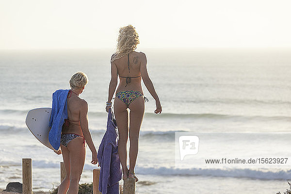 Two blonde girls with their surfboards and stand up paddle board checking the surf on the beach